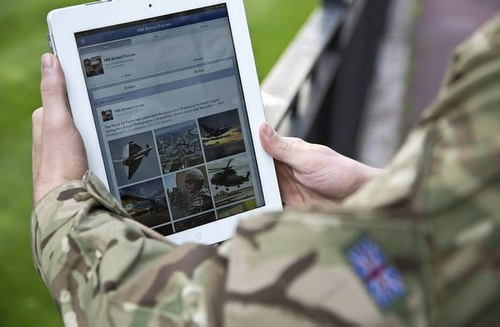 A serviceman accesses social media channels using an iPad, outside MOD Main Building in London