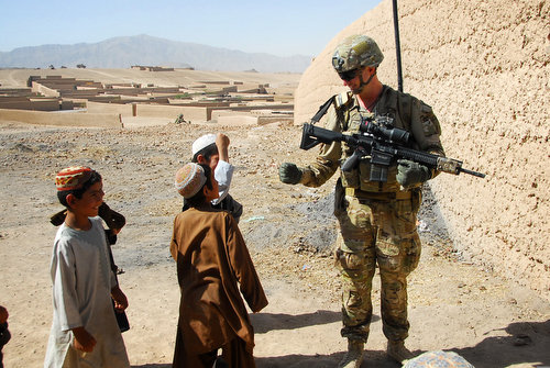 Australian Army Pvt. Levi Mooney, right, bumps fists with a child during a patrol in Tarin Kowt, Uruzgan province, Afghanistan, July 26, 2013. (U.S. Army National Guard photo by Sgt. Jessi Ann McCormick/Released)
