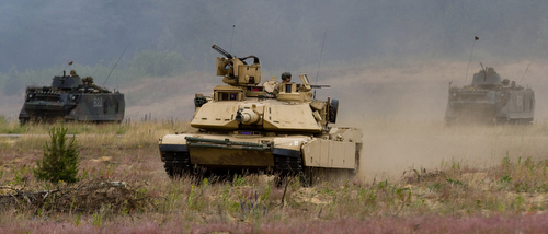A United States Army Abrams M1A2 Main Battle Tank leads the charge during a battle demonstration along with two Lithuanian Land Forces M113 Armored Personnel Carriers during the final day of Saber Strike 2015 at the Great Lithuanian Hetman Jonusas Radvila Training Regiment, June 18, 2015. Saber Strike is a long-standing U.S. Army Europe-led cooperative training exercise. This year's exercise objectives facilitate cooperation amongst the U.S., Estonia, Latvia, Lithuania, and Poland to improve joint operational capability in a range of missions as well as preparing the participating nations and units to support multinational contingency operations. There are more than 6,000 participants from 13 different nations. (U.S. Army Photo by Sgt. James Avery, 16th Mobile Public Affairs Detachment)