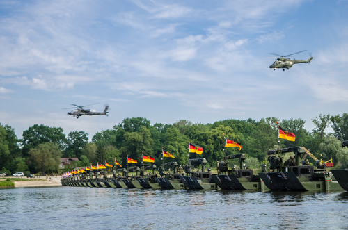 Helicopters fly over troops on a hasty bridge during a bridge crossing operation in Chelmno, Poland, June 8, 2016. Multinational forces coordinated, assembled and then traversed a bridge composed of German and British M3 Amphibious Rigs, allowing vehicles to cross the Vistula River as a part of Exercise Anakonda 2016. The Polish-led exercise is a collective training effort to reinforce interoperability and strengthen bonds between NATO allies and partners, ensuring collective peace and security in the region.
